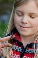 Mädchen, Kind hat eine Heidelibelle, Sympetrum spec. auf der Hand und beobachtet sie, Libellen sind ungefährlich und können nicht stechen!