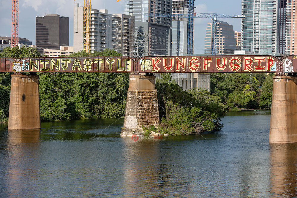 """AUSTIN, TEXAS - Visible from the Lady Bird Hike and Bike Trail the Austin Railroad Graffiti Bridge over Lady Bird Town Lake contains some of Austin's most famous and cherished graffiti mural paintings including the """"I've Got NINJA STYLE KUNG FU GRIP."""""""