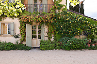 Climbing plants in full bloom adorn the side entrance and balcony of this large country house