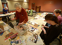NWA Democrat-Gazette/ANDY SHUPE<br /> Nancy Hartney (center) of Fayetteville speaks Wednesday, Jan. 10, 2018, with participants as she makes an envelope during a stationary-making workshop at the Fayetteville Public Library.