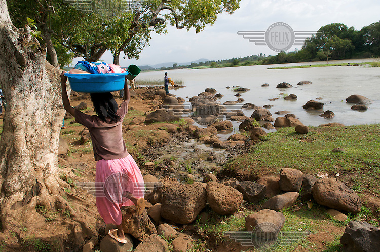 A woman carries her washing beside the Blue Nile River..