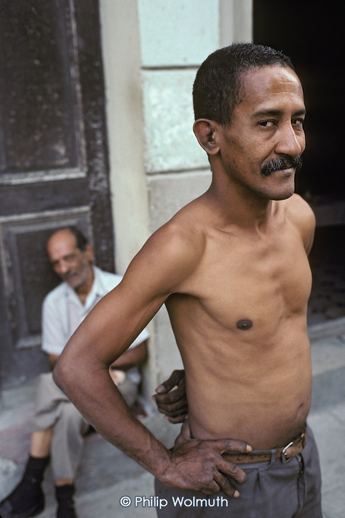 Manolo passes the afternoon with a friend outside his home in one of the decaying streets of Central Havana.