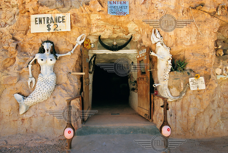 Entrance of Crocodile Harry's dugout, decorated with models of a crocodile and a mermaid.  Harry is a Latvian baron who emigrated to Australia in the 1940s and spent 13 years hunting crocodiles before digging for opals in the town, which is considered the capital for opal mining in Australia.