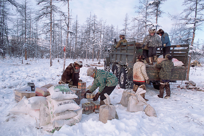Even reindeer herders unload supplies from a Ural truck at their winter camp. Northern Evensk, Magadan Region, E. Siberia, Russia
