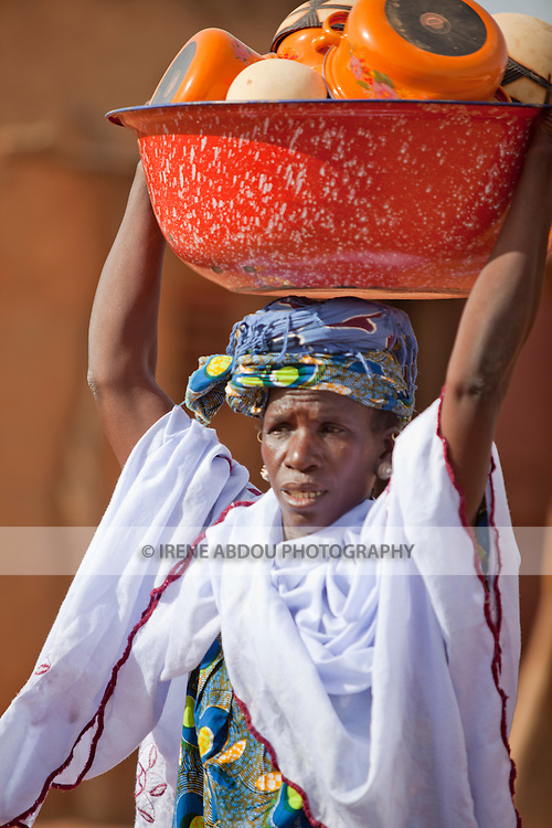 In the town of Djibo in northern Burkina Faso, a Fulani wedding has taken place.  Friends and family of the bride carry gifts and possessions of the bride - pots and pans, blankets, textiles, and other items - from the bride's home to her new home with her husband.  Surprisingly, many of these gifts are not destined for the bride or groom, but will be parceled out to wedding guests and relatives of the groom.