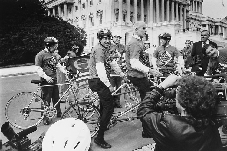 Members ride on the Capitol Hill grounds for 90 days to kick-off Earth Day. Rep. Bob Clement, D-Tenn., Rep. Howard Wolpe, D-Mich., and Rep. John Porter, R-Ill., on bipartisan tandem, Rep. Donald J. Pease, D-Ohio, Rep. Ben Cardin, D-Md., Rep. Sam Gejdenson, D-Conn., and Rep. George Gekas, R-Pa., in suit on Jan. 23, 1990. (Photo by Maureen Keating/CQ Roll Call)