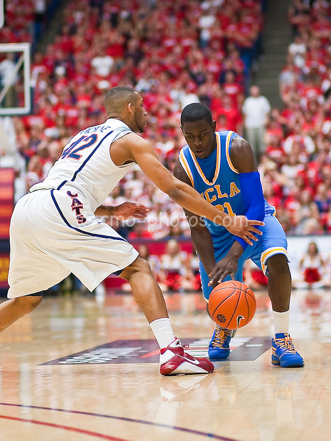 Feb 14, 2009; Tucson, AZ, USA; UCLA Bruins guard Jrue Holiday (21) tries to dribble past the outstretched arm of Arizona Wildcats forward Jamelle Horne (42) in the first half of a game at the McKale Center.  The Wildcats won the game 84-72 to break an eight-game losing streak against the Bruins and win their seventh game in a row.