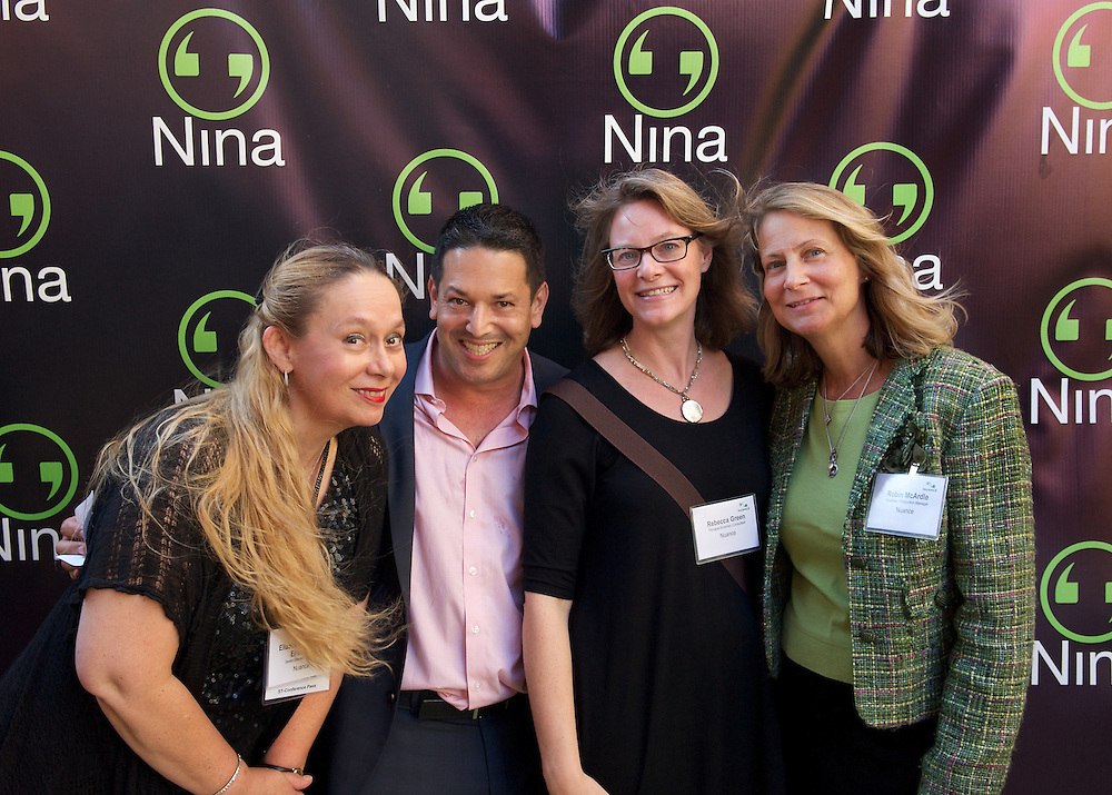 Guests posing in front of a branded backdrop at a corporate event for Nuance Communications.