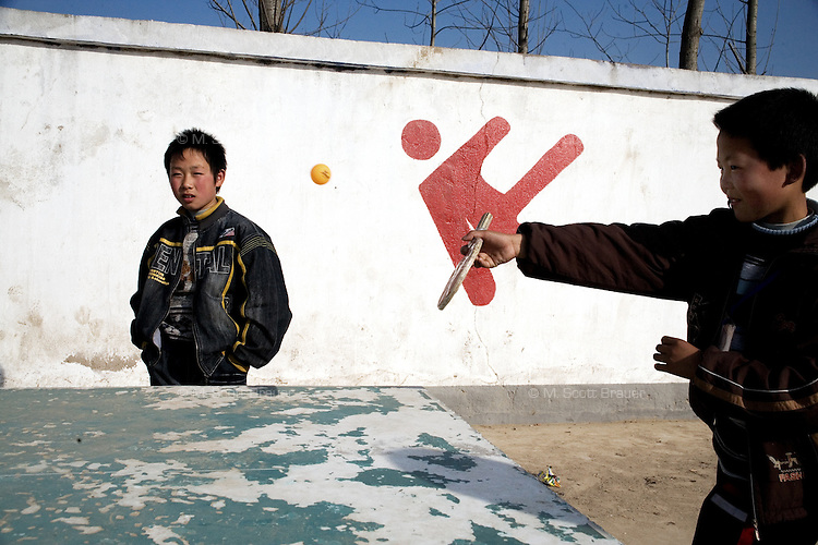 Schoolchildren play ping-pong in the schoolyard at Yixing Middle School in Lianshui County, Jiangsu Province, China.  The Pfrang Association, a German charity based in Nanjing, China, sponsors a number of children in the school, providing money for boarding, food, clothing, school supplies, and other necessities to continue schooling.  The majority of children at this school come from poor farming families in rural Jiangsu Province, China.