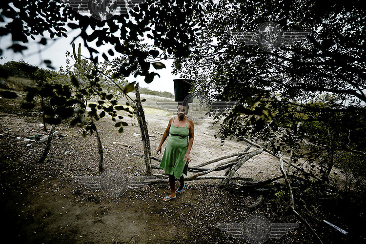 A woman carries a bucket of water on her head which she collected from an artifical lake used by local farmers.