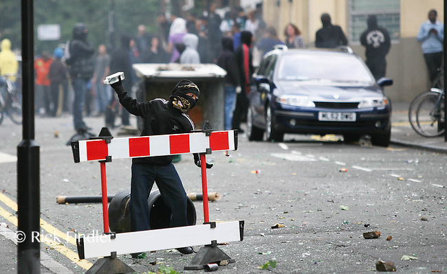 PH: Rick Findler..08.08.11 A young boy throws a glass bottle toward police as youths and police clash in Hackney today as riots spread across the whole of London including Croydon and Clapham.