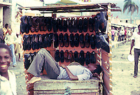 Shoeless boy asleep on his stall. Images of the capital,Port au Prince, Haiti 1975
