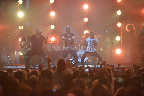 MIAMI, FL - NOVEMBER 05: Enrique Iglesias (C) and Alexander Delgado and Randy Malcom of Gente de Zona performs on stage at iHeartRadio Fiesta Latina at American Airlines Arena on November 5, 2016 in Miami, Florida. Credit: MPI10 / MediaPunch