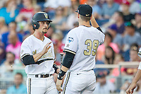 Vanderbilt Commodores outfielder Rhett Wiseman (8) is greeted by teammate Kyle Smith (39) after scoring against the TCU Horned Frogs in Game 12 of the NCAA College World Series on June 19, 2015 at TD Ameritrade Park in Omaha, Nebraska. The Commodores defeated TCU 7-1. (Andrew Woolley/Four Seam Images)