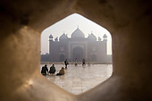 Agra, Uttar Pradesh, India. The Taj Mahal; main mausoleum; tourists and the Jawab building with its three domes outside seen through a lattice screen.