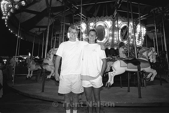 Two guys in front of the carnival merry-go-round.<br />