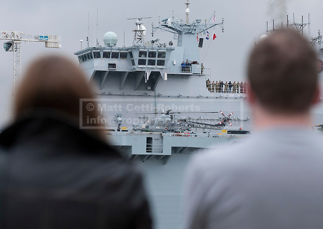 04/05/2012. LONDON, UK. Members of the public watch HMS Ocean, the Royal Navy's helicopter carrier, after she made her way up the Thames to moor in Greenwich, London, today (04/05/12). HMS Ocean has been deployed as part of an exercise involving the RAF, British Army and Royal Navy taking place across London as part of security preparations for the 2012 London Olympic Games. Photo credit: Matt Cetti-Roberts