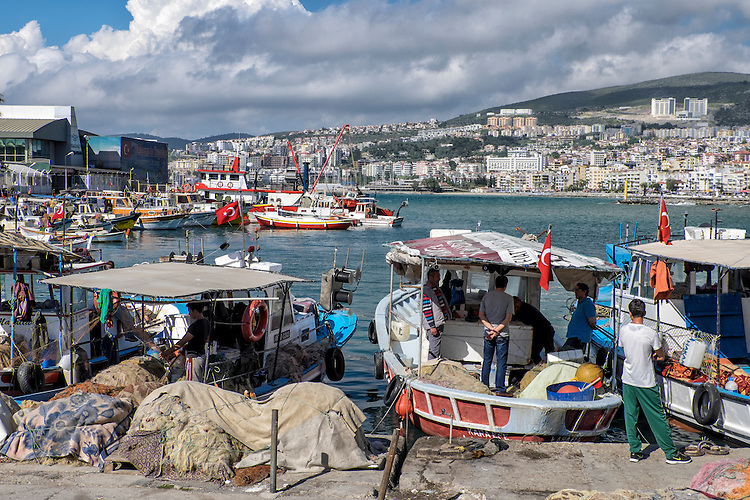 The main center of Kusadasi is upstaged by a busy small fishing boat harbor with mounds of nets laid out to dry.
