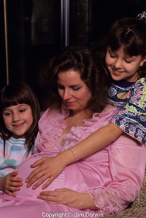 Pregnant mature woman sitting looking down while kids touch her baby