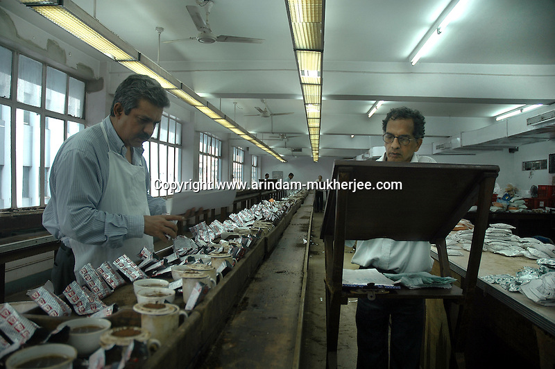 A tea tester and his assitant at work in the tea testing room of J. Thomas ltd. company in Kolkata, West Bengal,  India,  Arindam Mukherjee