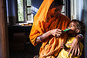 25 year old Dayawati (centre) feeds a dose of RUTF to her 17 month son, Naresh Mukhiya at the local health centre in Hanuman Nagar in Saptari, Nepal. <br /> Naresh Mukhiya was first admitted on July 17, 2013 when he was 9 months old. MUAC - 109 mm, Weight - 5.5kg, and Height - 65 cm. He was discharged on Oct 1st, 2013. MUAC at the time of discharge - 123, Weight - 6.5 Kg, Height - 66cm. Total RUTF consumes - 148 sachets.Gain of weight - 2gm.day.