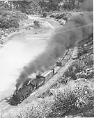 Elevated view of D&amp;RGW #498 leading a freight train through a canyon beside a river.<br /> D&amp;RGW