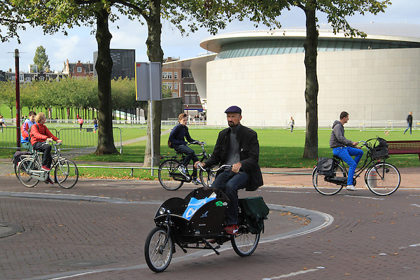 Biking at the Rjikmuseum, with the Van Gogh Museum behind, Amsterdam, Netherlands .  John offers private photo tours in Denver, Boulder and throughout Colorado, USA.  Year-round. .  John offers private photo tours in Denver, Boulder and throughout Colorado. Year-round.
