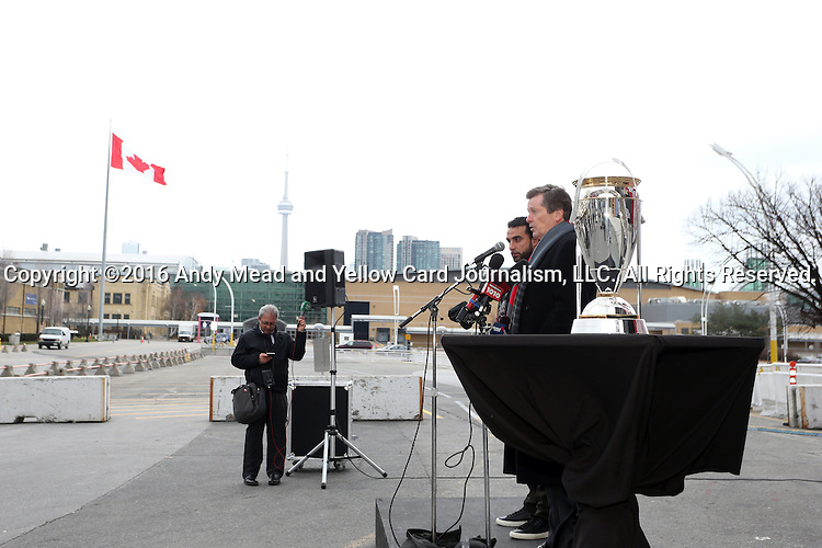 08 December 2016: Toronto mayor John Tory makes a speech flanked by Canadian soccer legend Dwayne De Rosario (behind) before the press conference. Major League Soccer's Philip F. Anschutz Trophy made an appearance with Toronto's mayor at a press conference outside of BMO Field in Toronto, Ontario in Canada two days before MLS Cup 2016.