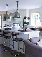 In the kitchen, the island has a top of honed Carrara marble, the wall tiles are by Waterworks, the stove is Viking, and the stools are by York Street Studio and the 1920s English pendants are from BK Antiques.
