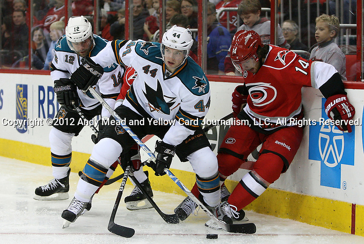 17 February 2012: San Jose's Marc-Edouard Vlasic (44) pulls the puck away from Carolina's Andreas Nodl (AUT) (14), and San Jose's Patrick Marleau (12). The Carolina Hurricanes played the San Jose Sharks at the RBC Center in Raleigh, North Carolina in a 2011-2012 National Hockey League regular season opening game.
