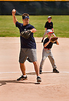 A coach prepares to throw the ball to a hitter during a coach pitch little league game.