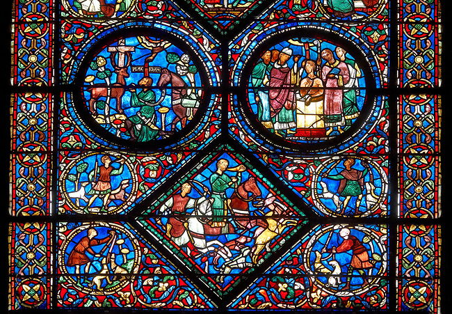 Medieval stained glass Window of the Gothic Cathedral of Chartres, France - dedicated to the life of St Anthony of the Desert.  Bottom central diamond panel -Placidus and a companion hunting deer , Top left oval - Placidus hears the words of Christ coming from the mouth of a stag, top right oval - Placidus is baptised and given the name 'Eustace'. A UNESCO World Heritage Site.