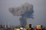 """Smoke rises following an Israeli air strike in Gaza City on August 23, 2014. Hamas-led gunmen in Gaza executed 18 Palestinians accused of collaborating with Israel on Friday, accelerating a crackdown on suspected informers after Israeli forces tracked down and killed three senior Hamas commanders. Israeli Prime Minister Benjamin Netanyahu threatened to escalate the fight against Hamas, vowing the group would """"pay a heavy price"""" after a four-year-old Israeli boy was killed by a mortar attack from Gaza, the first Israeli child to die in the six-week conflict. Since the conflict began last month, 2,071 Palestinians, many of them civilians, have now been killed and around 400,000 of the enclave's 1.8 million people displaced. Sixty-four Israeli soldiers and four civilians in Israel have been killed. Photo by Yasser Qudih"""