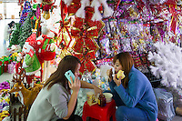 November 27, 2015, Yiwu China - Two female vendors eat lunch in front of booths displaying Christmas decorations inside the Festival Arts section of the Yiwu International Trade Market. Yiwu International Trade Market is the world's largest whole sale market for small commodities. Christmas decorations are available for bulk purchase all the year round.Photo by Dave Tacon / Sinopix