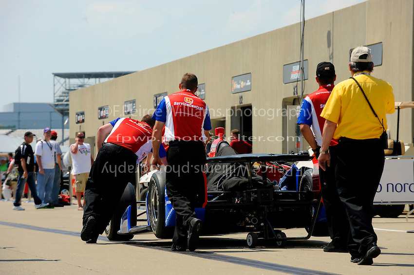 "The car of Graham Rahal (#38) is rolled back to it's garage under the watchful eye of a ""yellow shirt""."
