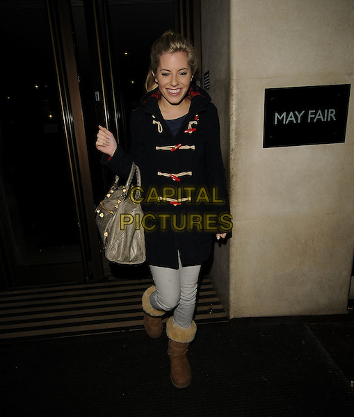 MOLLIE KING Of The Saturdays.At the Mayfair Hotel, London, England, UK, 16th January 2010..full length uggs ugg boots duffle duffel coat navy blue pale denim skinny jeans Balenciaga grey gray bag red toggles smiling walking .CAP/CAN.©Can Nguyen/Capital Pictures