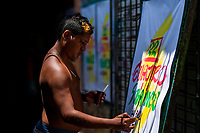"""A Colombian sign painter writes with a brush while working on music party posters in the sign painting workshop in Cartagena, Colombia, 17 April 2018. Hidden in the dark, narrow alleys of Bazurto market, a group of dozen young men gathered around José Corredor (""""Runner""""), the master painter, produce every day hundreds of hand-painted posters. Although the vast majority of the production is designed for a cheap visual promotion of popular Champeta music parties, held every weekend around the city, Runner and his apprentices also create other graphic design artworks, based on brush lettering technique. Using simple brushes and bright paints, the artisanal workshop keeps the traditional sign painting art alive."""