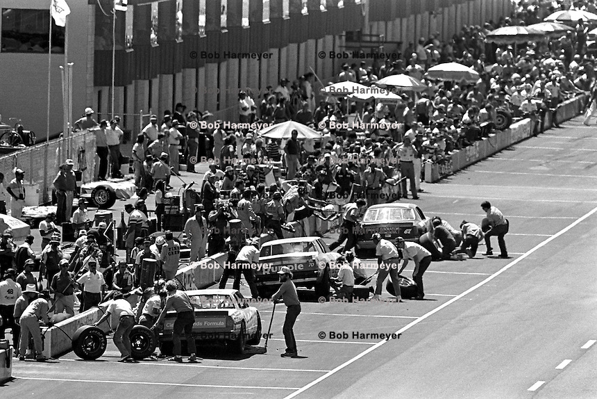 BROOKLYN, MI - AUGUST 11: A trio of cars make pit stops during the Champion Spark Plug 400 NASCAR Winston Cup race at the Michigan International Speedway near Brooklyn, Michigan, on August 11, 1985...