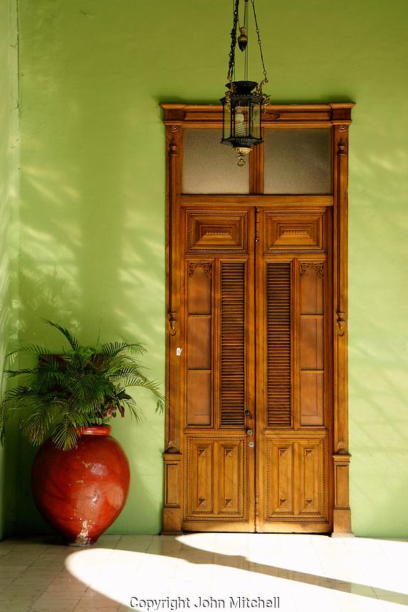 Spanish colonial wooden door and potted plant, Palacio de Gobierno or Government Palace, Merida, Yucatan, Mexico.