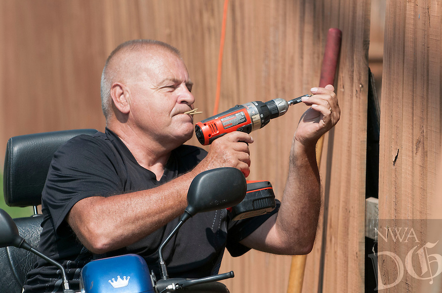 NWA Democrat-Gazette/J.T. WAMPLER  Ted Morrall of Lowell repairs his fence Sunday July 24, 2016. Morrall, an eighteen year resident of Lowell, originally moved from near Green Bay Wisconsin.