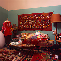 A floral pattern wall hanging in vibrant reds and orange hangs on the wall of a retro living room. A coffee table stands in front of a sofa covred with a rug.