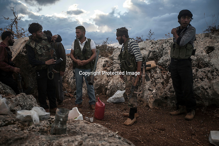 In this Thursday, Oct. 03, 2013 photo, opposition fighters belonging to AHMED KALE (left centre) rebel group, son of MOHAMMED AHMED KALE (not pictured), mount guard at the fronline outskirst Kafr Lata, a ghost village in a top of a mountain subdued under heavy shelling and bormbardments due the fighting between opposition fighters and government forces in the Idlib province countryside of Syria. Mohammed's whole family, included his six sons with their families and four daughters, is one of two families, that refuse to leave the village despite the heavy bombardments as four of his sons fight at the frontline situated one km from home. (AP
