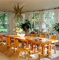 A Mexican pendant light hangs above a 1930s table and chairs in the dining room in which is displayed a collection of German mercury-glass ornaments