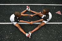 Two young boys help each other stretch out before competing in a running race at a track and field event.
