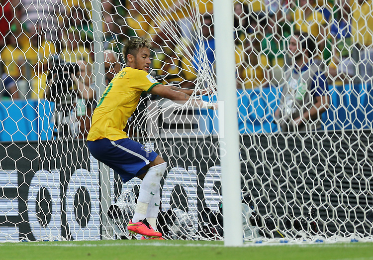 Brazil's Neymar gets caught up in the net after going close to scoring