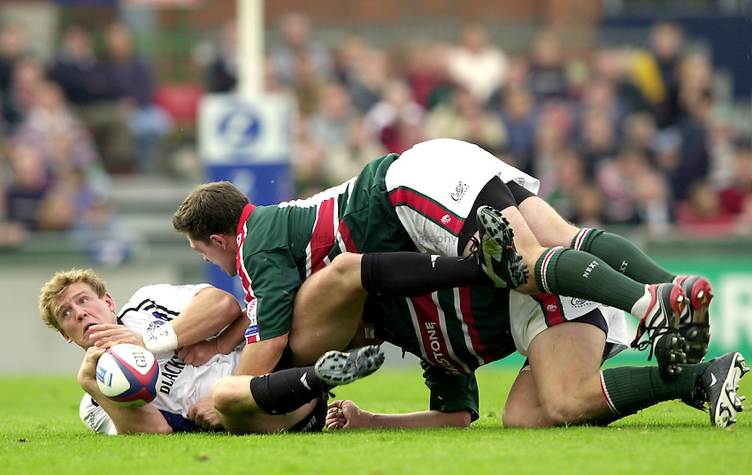 Photo. Richard Lane. .Leicester Tigers v Bath Rugby. Zurich Premiership. 05/10/2002.Mike Tindall  is brought down by the Leicester defence.