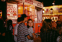 "Midway entertainment captivates even multi-media-jaded teenagers. Boys and girls at the Brazoria County Fair in Texas enjoy a little romance, a little comedy, and a little playful revenge as ""bozo"" the clown strafes the crowd with jocular insults."