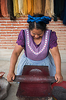 Maria Luisa Mendoza de Cruz (Fidel's wife) grindes the cochinilla insect in preparation to be used to dye the wool purple, in her house and workshop Casa Cruz, Avenida Juarez 190, Teotitlan del Valle, Oaxaca, Mexico