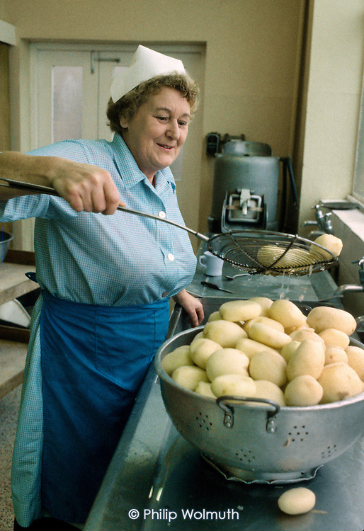 A dinner lady, employed by the Local Education Authority, prepares potatoes in a school kitchen in London. The school meals service was mostly contracted out to private contractors in the 1980's.