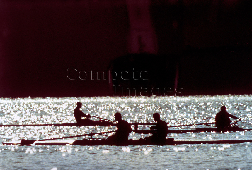 3 sets of rowers in silhouette on a river at dusk